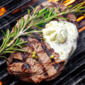 steak with butter on grill